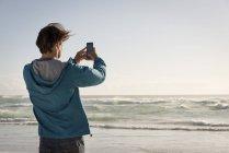 Jovem feliz tirando foto com telefone celular na praia — Fotografia de Stock