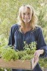 Ritratto di giovane donna bionda che trasporta cassa di piante in giardino — Foto stock