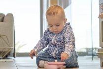 Close-up de menina brincando com brinquedo no chão em casa — Fotografia de Stock