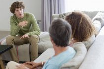 Boy talking to parents while sitting on sofa in living room at home — Stock Photo