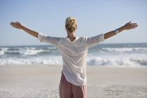 Relaxed woman with arms outstretched standing on sunny beach — Stock Photo