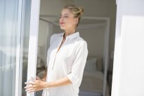 Jovem mulher relaxada com os olhos fechados em pé na janela à luz do sol — Fotografia de Stock