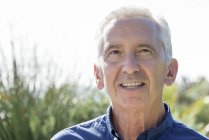 Портрет заботливого пожилого человека, улыбающегося в саду — стоковое фото