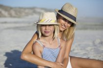 Portrait of happy woman and daughter sitting on beach — Stock Photo