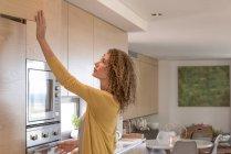 Женщина в повседневной одежде открывает ящик на кухне — стоковое фото