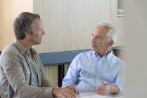 Homme principal discutant avec un conseiller financier à la maison — Photo de stock