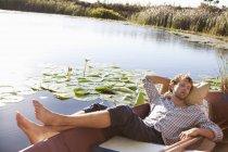 Giovane rilassato che dorme in barca sul lago in campagna — Foto stock