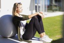 Giovane donna rilassante mentre appoggiato sulla palla di pietra all'aperto — Foto stock