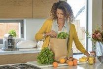 Женщина достает еду из бумажного пакета на кухне — стоковое фото