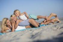 Молодая женщина наслаждается на песчаном пляже с детьми — стоковое фото