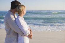 Мечтательный мужчина обнимает женщину на морском пляже — стоковое фото