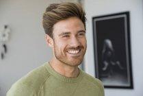Закри усміхнений бородатий юнак фотографіях хтось дивитися вбік — стокове фото