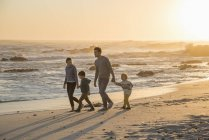 Família feliz andando na praia de areia ao pôr do sol — Fotografia de Stock