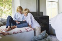 Children using digital tablet on sofa at home — Stock Photo