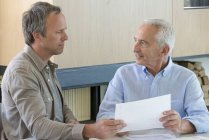 Встреча старшего человека с финансовым консультантом дома — стоковое фото