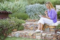 Young woman reading book in garden with hand on chin — Stock Photo