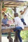 Opinião traseira a corda de agarramento do menino para alcangar a casa da árvore com amigos — Fotografia de Stock