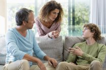 Family resting and talking in living room at home — Stock Photo
