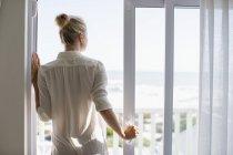 Junge Frau steht am Fenster in Haus an der Küste — Stockfoto