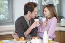 Мужчина пьет чай с дочерью на кухне — стоковое фото
