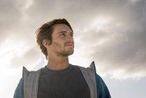 Портрет молодого человека, смотрящего на облачное небо — стоковое фото