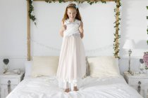 Portrait of a girl standing on bed and trying dress — Stock Photo