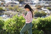 Flor de explotación la mujer caminando en vegetación verde - foto de stock