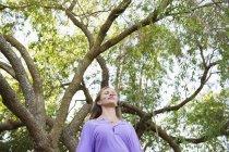 Joven mujer relajada de pie bajo el árbol verde - foto de stock