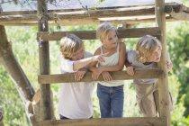 Crianças sorridentes olhando para longe da casa da árvore no jardim de verão — Fotografia de Stock