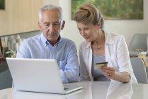Senior pareja de compras en línea con el ordenador portátil en casa - foto de stock