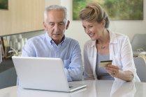 Couple de personnes âgées courses en ligne avec ordinateur portable à la maison — Photo de stock