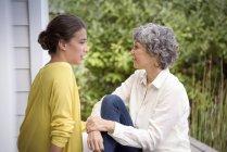 Мать разговаривает со взрослой дочерью на крыльце — стоковое фото