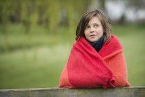 Retrato de menina sorridente envolto em cobertor de pé em campo sobre fundo borrado — Fotografia de Stock
