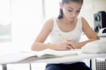 Сосредоточенная девочка-подросток учится за столом — стоковое фото