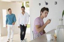 Jeune homme prenant un café à la maison avec des amis marchant sur le fond — Photo de stock