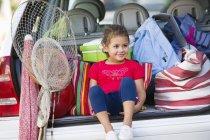 Милая маленькая девочка сидит в багажнике с вещами для отпуска — стоковое фото