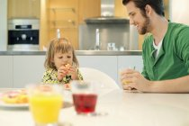 Man and daughter having breakfast at table at home — Stock Photo