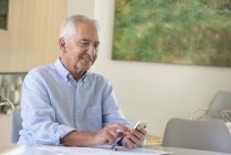 Счастливый пожилой человек пользуется мобильным телефоном, делая бумажную работу дома — стоковое фото