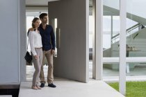 Casal em pé à porta da casa e olhando para longe — Fotografia de Stock