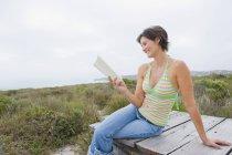 Femme souriante assise sur une promenade dans la nature et lisant un livre — Photo de stock