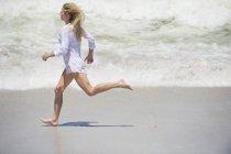 Femme blonde dans la chemise fonctionnant sur la plage — Photo de stock