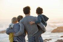 Visão traseira da família olhando para o mar na praia ao pôr do sol — Fotografia de Stock