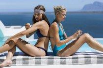Jóvenes amigas aplicando cremas solares en la piel junto a la piscina - foto de stock