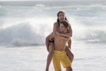 Счастливая молодая женщина катается на спине на плечах парня на пляже — стоковое фото