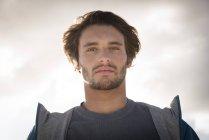 Портрет молодого человека, смотрящего в камеру на облачном небе — стоковое фото
