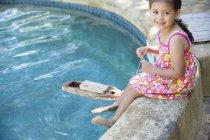 Chica sentada en el borde de la piscina con barco de juguete en el agua - foto de stock