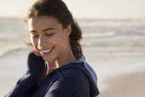 Улыбающаяся молодая женщина в толстовке, смотрящая вниз на пляж — стоковое фото