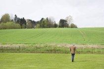 Homem usando telefone celular em campo verde — Fotografia de Stock