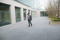 Messaggi di testo uomo d'affari sul telefono cellulare all'aperto edificio per uffici — Foto stock