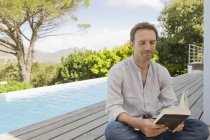 Homem leitura livro no jardim perto da piscina — Fotografia de Stock